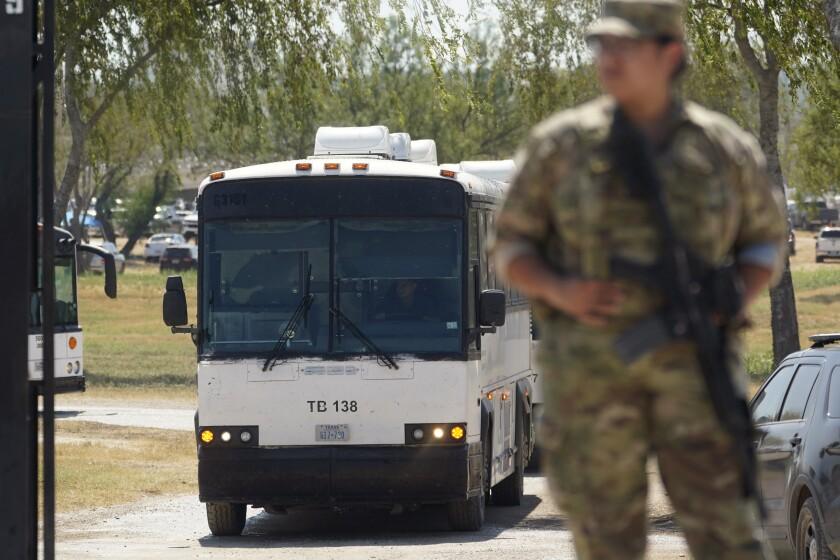 Un Guardia Nacional vigila en una puerta a lo largo de una valla fronteriza