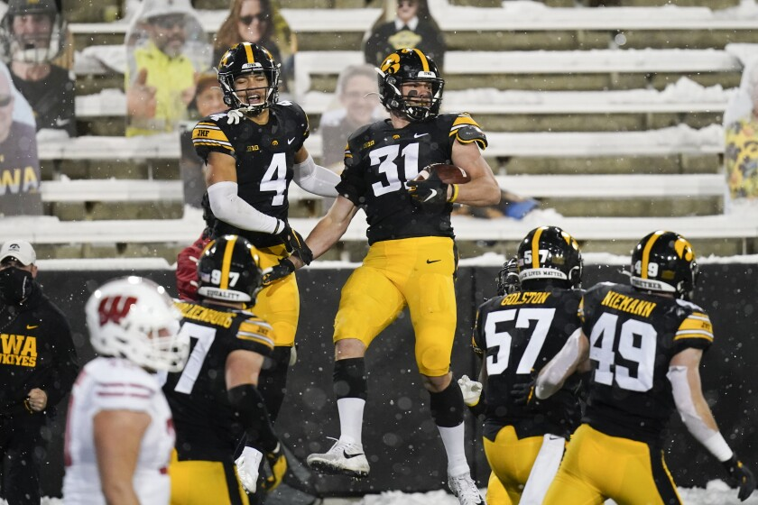 Iowa linebacker Jack Campbell (31) celebrates with teammate Dane Belton (4) after intercepting a pass during the second half of an NCAA college football game against Wisconsin, Saturday, Dec. 12, 2020, in Iowa City, Iowa. Iowa won 28-7. (AP Photo/Charlie Neibergall)