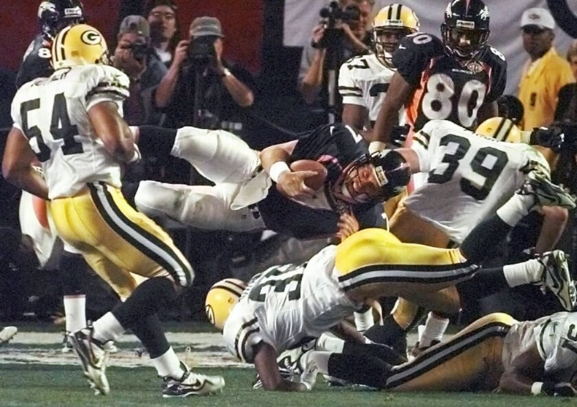 FILE - In this Jan. 25, 1998, file photo, Denver Broncos quarterback John Elway is upended Green Bay Packers' Brian Williams (51) and Elroy Butler (36) while running for a first down during the third quarter of NFL football's Super Bowl XXXII in San Diego. The play extended a drive that resulted in a touchdown that broke a tie. (AP Photo/Elise Amendola, File)