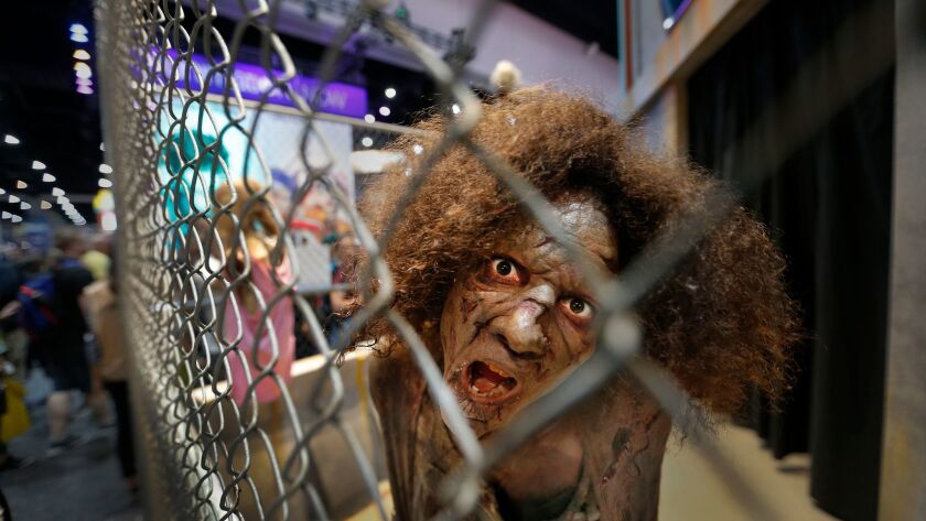 """A zombie actor from the AMC series """"The Walking Dead"""" approaches visitors at Comic-Con International 2017 in San Diego."""