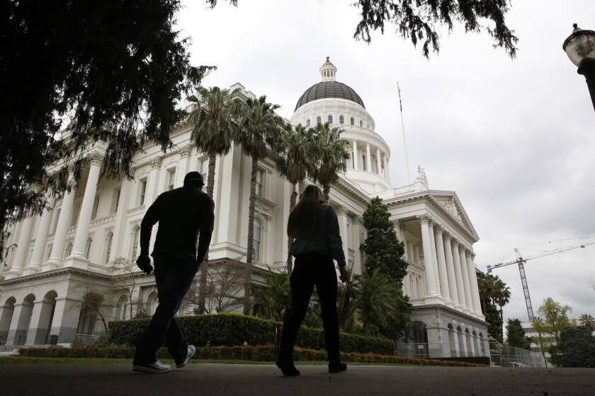 People walk near the Capitol in Sacramento