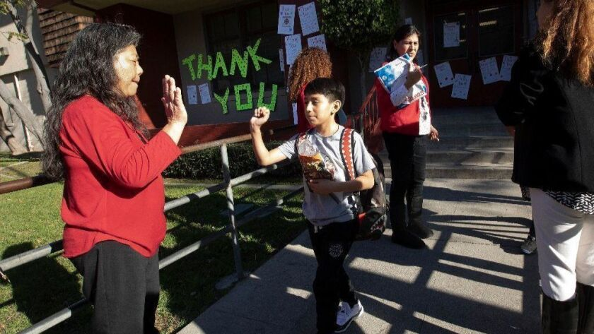 A fifth-grader greets a teacher at Union Avenue Elementary School on the first day teachers returned from their strike.