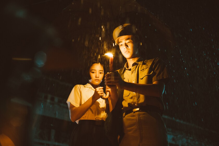 A female and a male high school student under an umbrella with a candle.