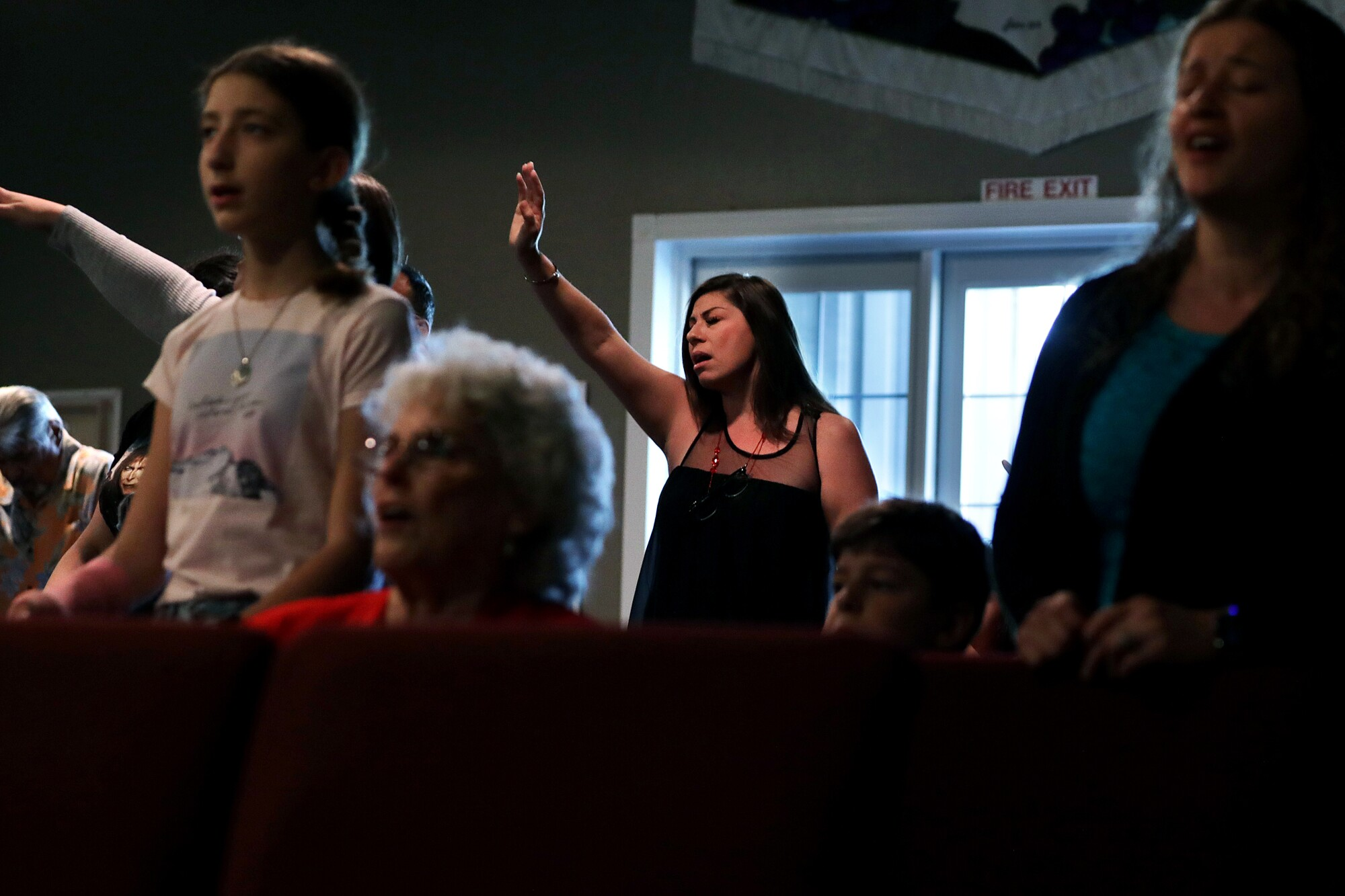 Worshipers, including Cindy Meddinna, center, gather for a service at Bundy Canyon Christian Church in Wildomar, Calif.