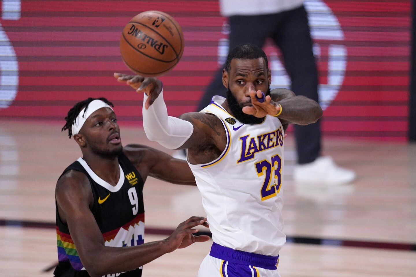 Lakers forward LeBron James, right, passes in front of Denver Nuggets forward Jerami Grant during the first half of Game 3.