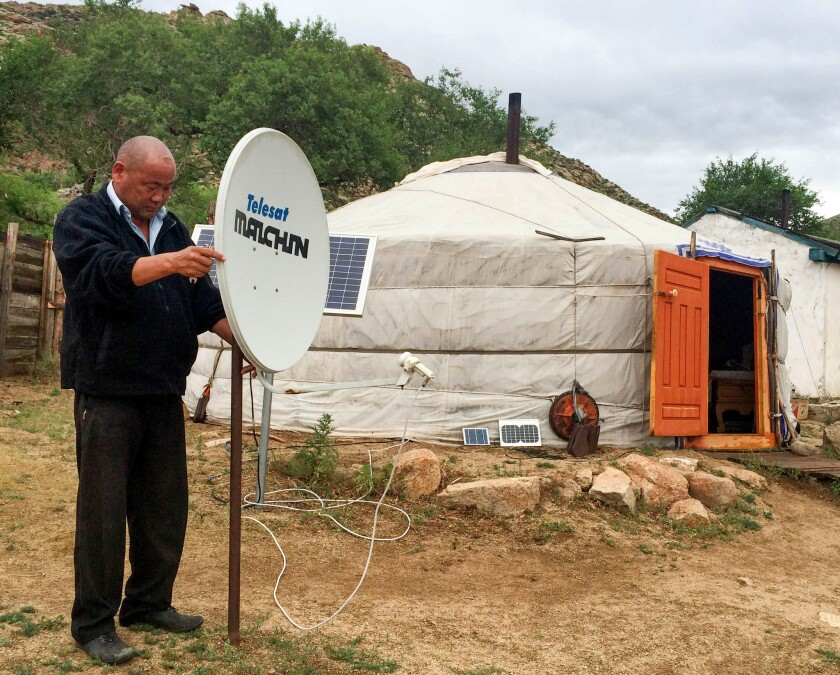 "Tsagaana Davaa adjusts the solar-powered satellite dish outside his yurt in a remote part of Mongolia. He gets more than 60 stations, offering everything from ""Breaking Bad"" to Hollywood blockbusters."