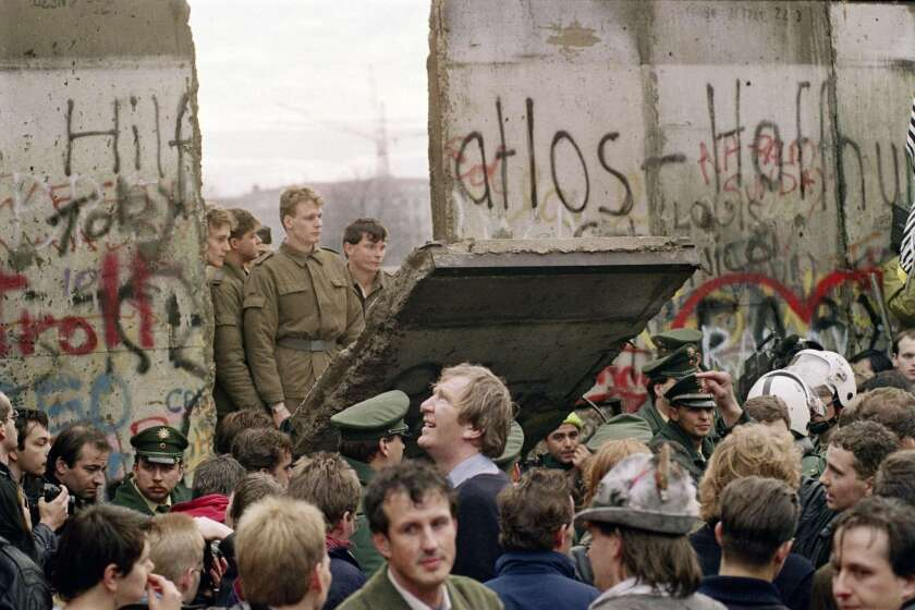 West Berliners crowd in front of the Berlin Wall as they watch East German border guards demolishing a section of the wall in order to open a new crossing point between East and West Berlin in 1989.
