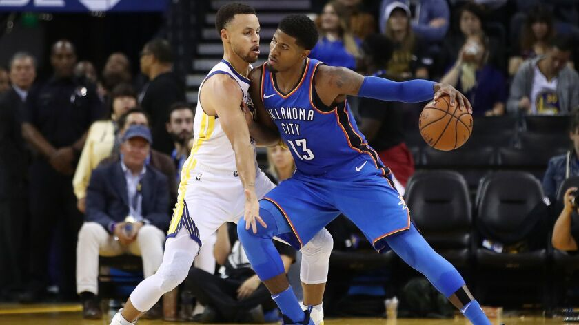 Oklahoma City's Paul George, right, drives with the ball against Golden State's Stephen Curry during the game on Tuesday in Oakland.