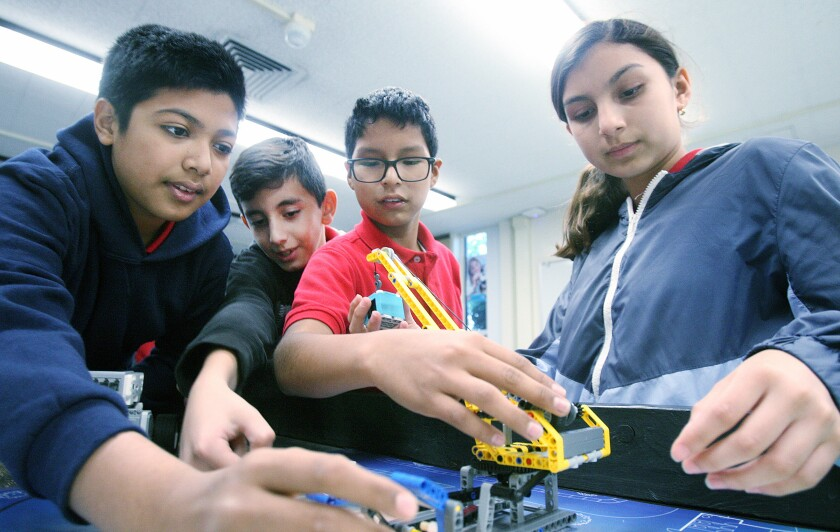 Ibrahim Ahmad, 13, Avakeem Avakian, 11, Alexander Sebastian, 12, and Diana Lopez, 12, work together on a Lego robot in Randy Kamiya's robotics classroom at Roosevelt Middle School on Monday.