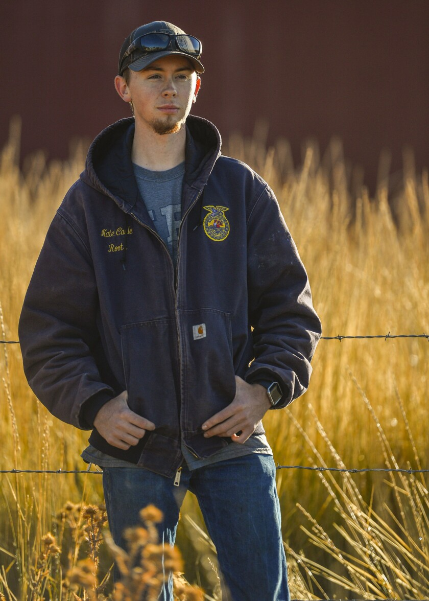 Nate Cable, a 12th grader at Roots Charter High School, poses for a portrait at the school's farm on