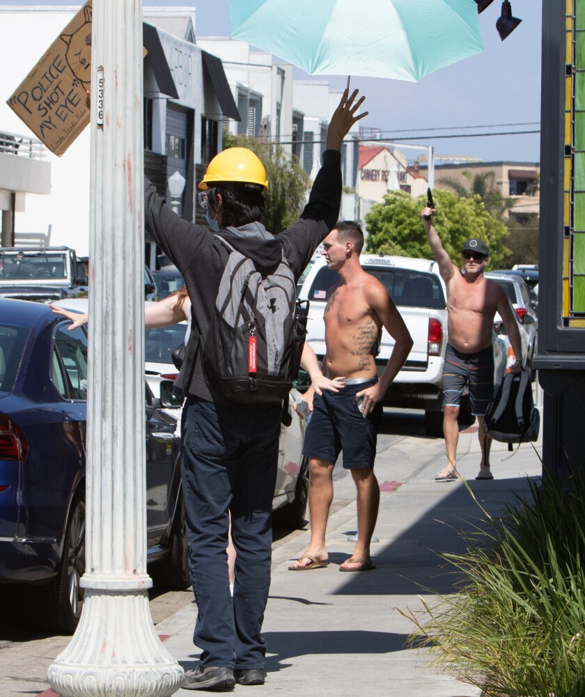 Travis Patrick White, right, pulls out a handgun from his backpack and holds it up Wednesday in Newport Beach.