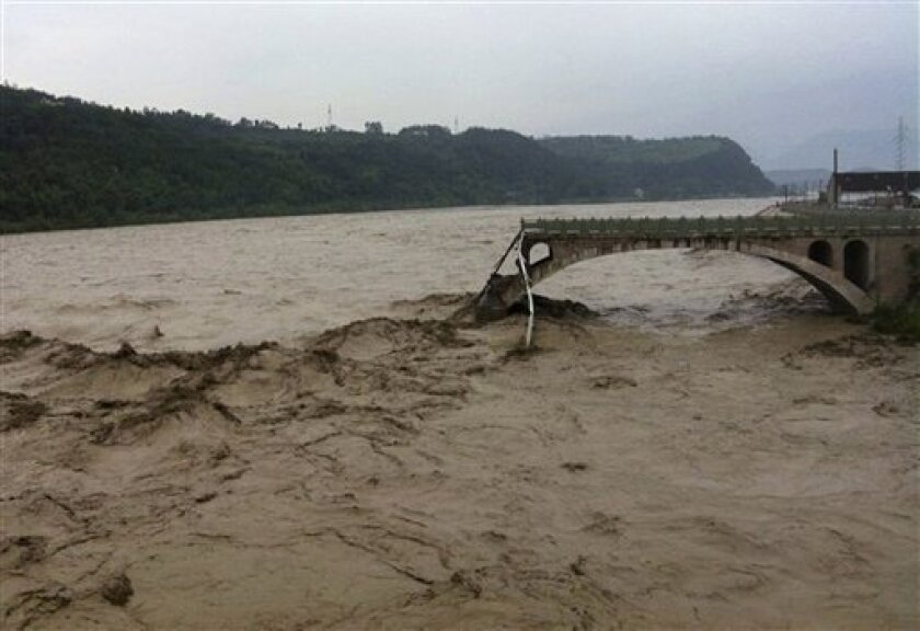 In this image taken by mobile phone camera, what remains of the Qinglian bridge that was swept away by heaving flood waters is seen in the city of Jiangyou in the western province of Sichuan on Tuesday, July 9, 2013. Three cars and a delivery van fell into the torrent when the nearly 50-year-old Qinglian bridge broke apart just before noon in the city of Jiangyou in the western province of Sichuan, the local government said in a statement posted on its official website. (AP Photo) CHINA OUT