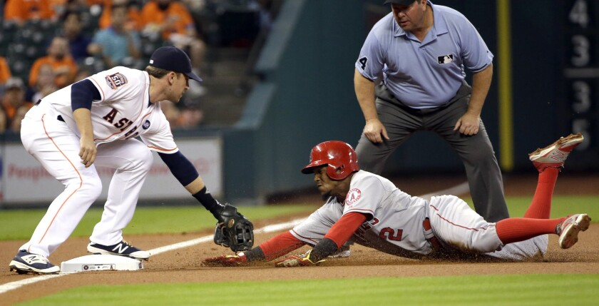 Angels shortstop Erick Aybar is tagged out by Astros third baseman Jed Lowrie while trying to take two bases on a wild pitch.