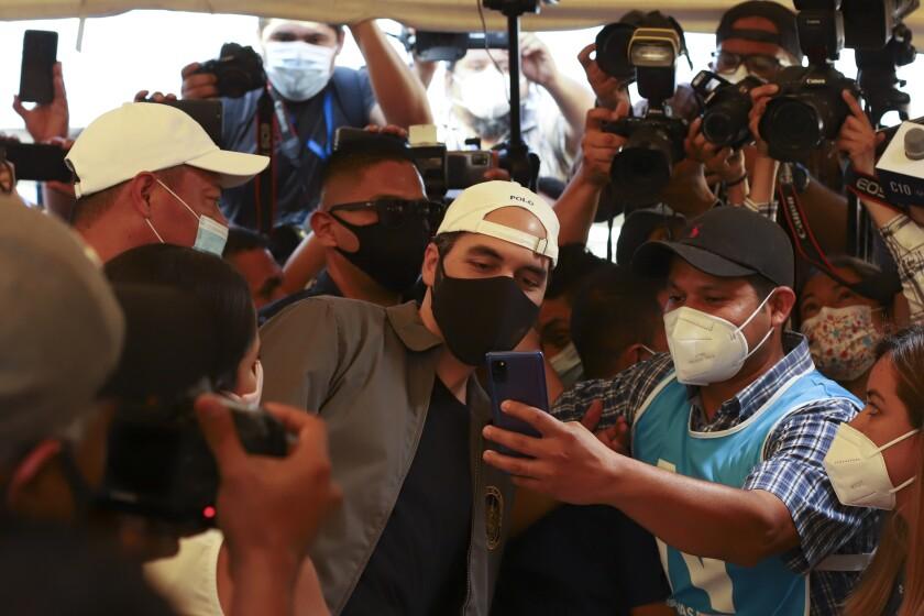 El presidente Nayib Bukele posa para una selfie con un trabajador electoral