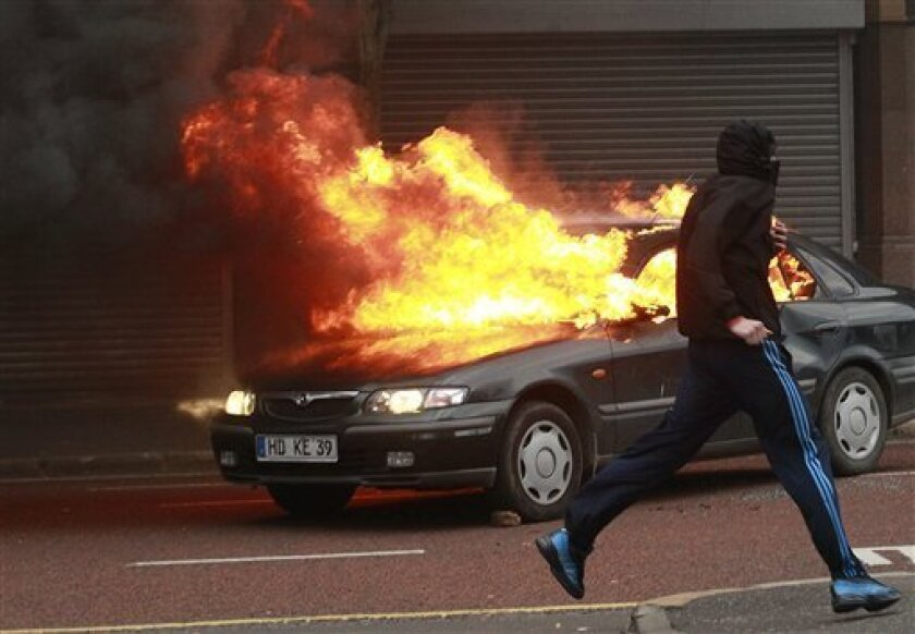 A Loyalist protester runs past a burning car during rioting in the centre of Belfast, Northern Ireland, Friday, Aug. 9, 2013. A number of people, including police officers, have been injured during trouble in Belfast city centre linked to a republican anti-internment parade. Loyalist protesters attacked the police as they waited for the republican parade to arrive. (AP Photo/Peter Morrison)