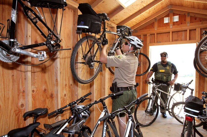 San Marcos Sheriff's Dept. Bicycle Patrol Deputy Dustin Nelson stows one of the Dept.'s new bikes in the new storage shed for the bikes at the station. At right is Deputy Alfred Gathings.