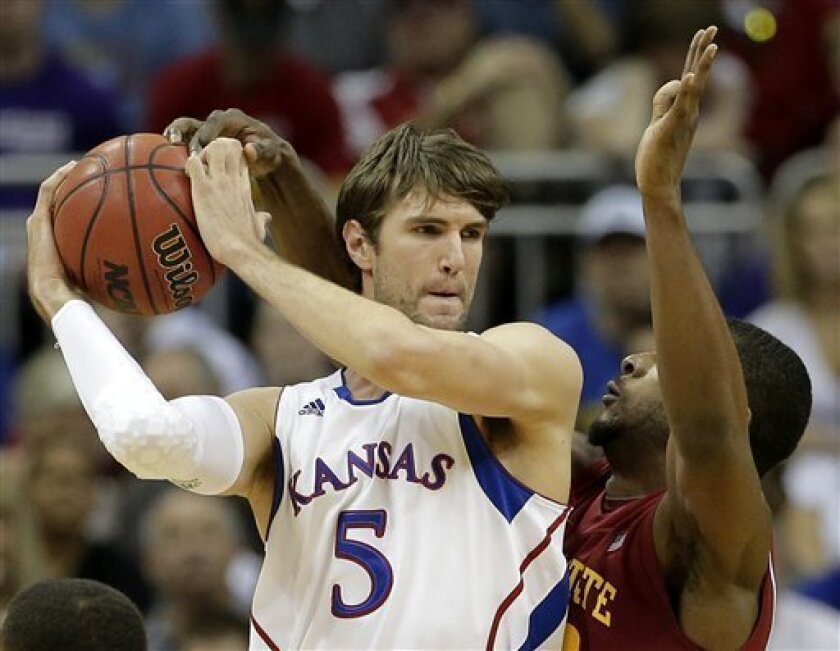 Kansas center Jeff Withey (5) looks to pass the ball around Iowa State forward Anthony Booker during the first half an NCAA college basketball game in the Big 12 men's tournament on Friday, March 15, 2013, in Kansas City, Mo. (AP Photo/Charlie Riedel)