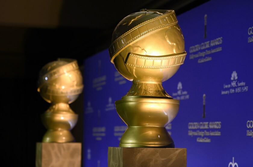Golden Globe trophies against a blue backdrop