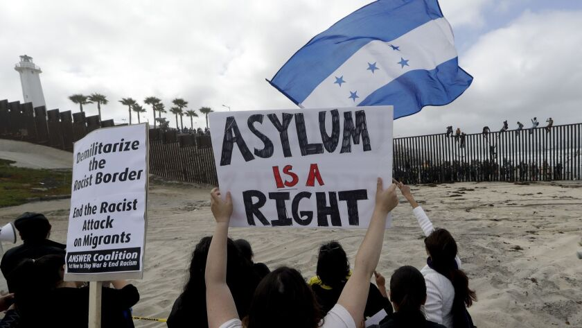 Migrants and their supporters gathered at the border fencing between California and Tijuana.