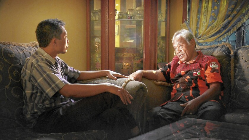 """Adi Rukun questions Amir Siahaan, one of the death squad leaders responsible for his brother's death during the 1960s Indonesian massacres, in Joshua Oppenheimer's """"The Look of Silence."""""""