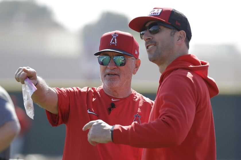 Angels manager Joe Maddon talks with general manager Billy Eppler during spring training on Feb. 17 in Tempe, Ariz.