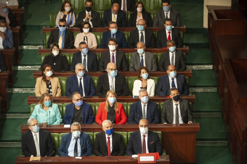 Tunisian designated Prime Minister Hichem Mechichi, first row at right, sits with members of his cabinet at the parliament before a confidence vote in Tunis, Tuesday, Sept. 1, 2020. (AP Photo/Riadh Dridi)