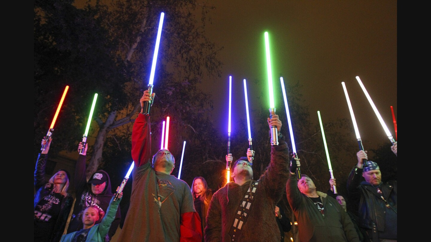 Star Wars fans raise their lightsabers in tribute to actress Carrie Fisher at the California Center for the Arts in Escondido on Friday.