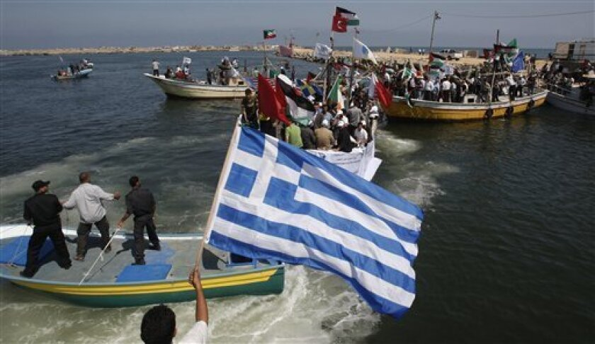 Palestinians ride boats and wave flags of various countries, in Gaza port, a day before a flotilla of aid ships is expected to try to sail into the blockaded territory, in Gaza city, Sunday, May 30, 2010. Hundreds of pro-Palestinian activists on seven ships were to set sail for the Gaza Strip on Su