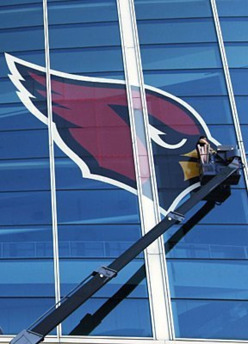 Jeff Watkins, from Detroit, Mich., puts up decorative emblems on Raymond James Stadium in preparation for Sunday's Super Bowl between the Pittsburgh Steelers and Arizona Cardinals in Tampa, Fla.