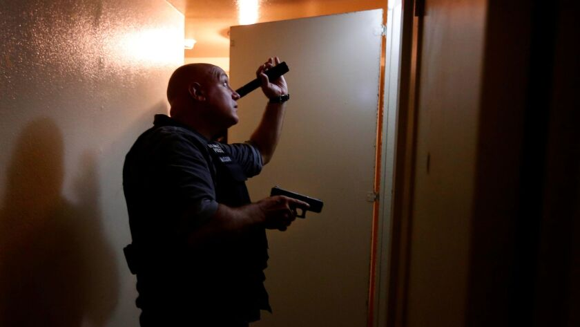 Sgt. Stephen McClean searches an apartment in South L.A. after shots were fired at the building.