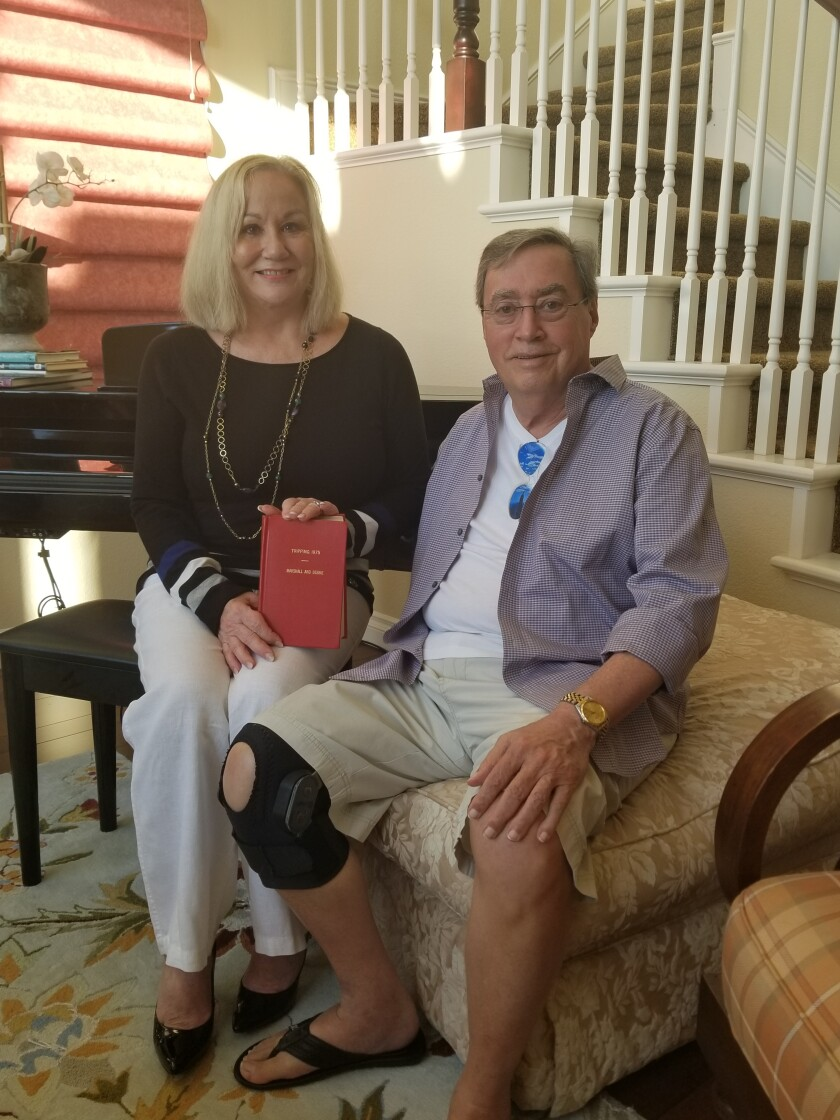 Debbie and Marshall Hockett in their living room in Encinitas, with their original travel journal.