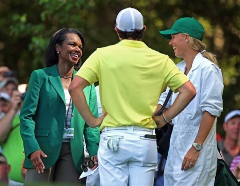 Condoleezza Rice, left, former Secretary of State and Augusta National member, laughs with Rory McIlroy, center, and his girlfriend Caroline Wozniacki on the sixth tee box during the par-three contest before the Masters golf tournament, Wednesday, April 10, 2013, in Augusta, Ga. Wozniacki caddied f