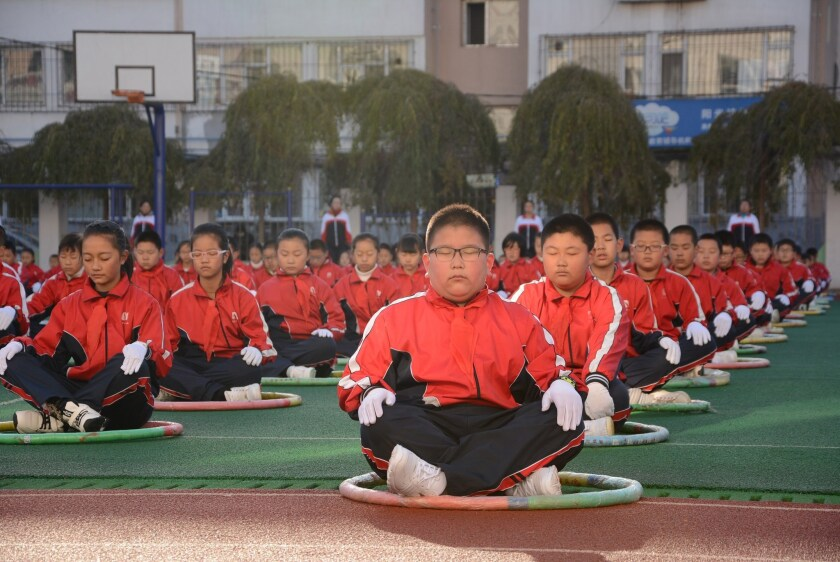 This photo taken Tuesday shows pupils exercising on the playground during a break at an elementary school in Jilin, in northeast China's Jilin province.