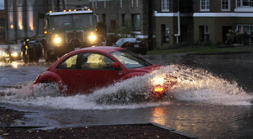 Cars and trucks navigate through standing water Monday at an intersection in Tacoma, Wash.