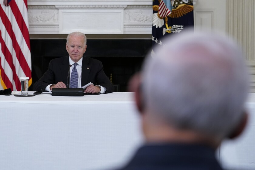 President Joe Biden, left, looks over towards Sen. Bob Menendez, D-N.J., right, during a meeting with Cuban-American leaders in the State Dining Room of the White House in Washington, Friday, July 30, 2021. (AP Photo/Susan Walsh)