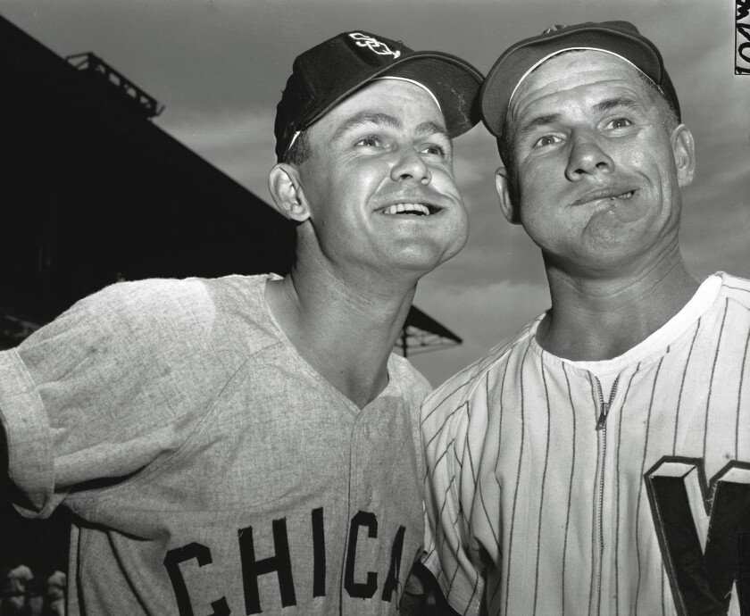 Chicago White Sox second baseman Nellie Fox, left, and Washington Senators shortstop Rocky Bridges pose with bulging wads of chewing tobacco before a game at Washington on Aug. 1, 1957. A California lawmaker wants to ban chewing tobacco from all levels of organized baseball in the state.