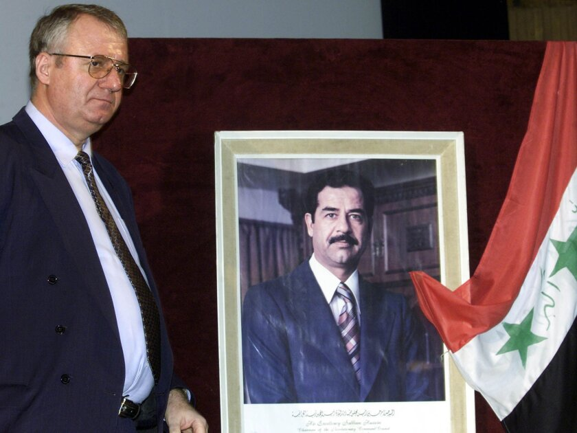 In this Jan. 25, 2003 file photo, Serbian ultranationalist leader, Vojislav Seselj, walks past a photo showing former Iraqi president Saddam Hussein, and an Iraqi flag following a rally against the U.S. plans on invasion in Iraq. The judgment in Seselj's case at the U.N. war crimes court is scheduled for Thursday, March 31. (AP Photo/Mikica Petrovic, File)