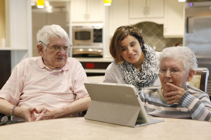 Seniors may be just as good as youngsters at processing visual information, but they may not be able to filter out what's irrelevant to the task, a new study suggests. Here, a recreation director in West Chester, Pa., works trivia questions on a tablet with seniors.
