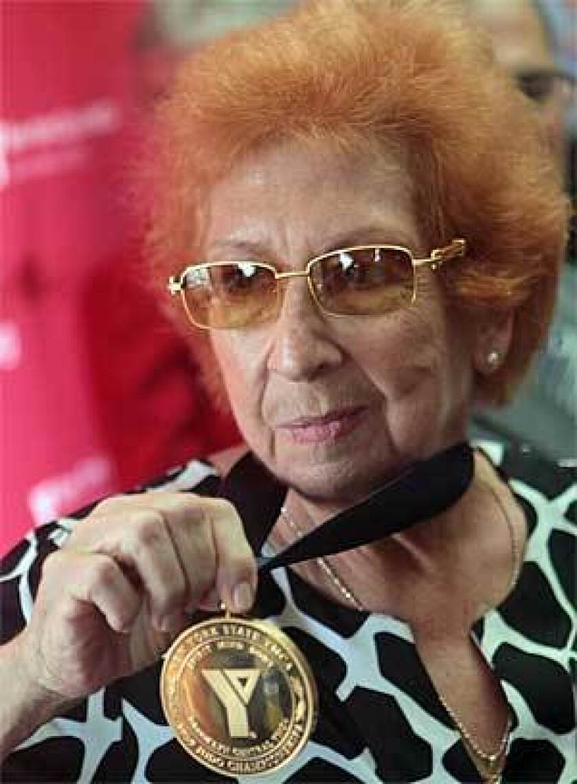 Kanokogi shows her gold medal for the 1959 New York State YMCA Judo Championships. Fifty years earlier she was stripped of the gold medal in the competition after judges realized she was a woman fighting against men.