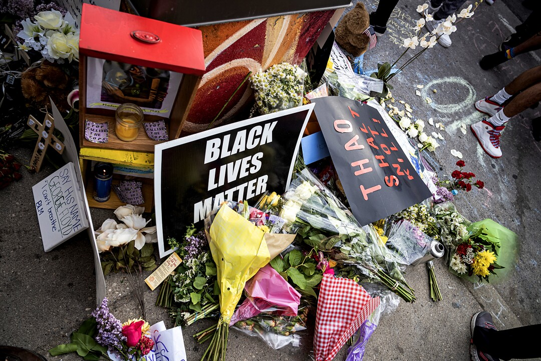 """Flowers and """"Black Lives Matter"""" signs are left at the site of Floyd's arrest."""