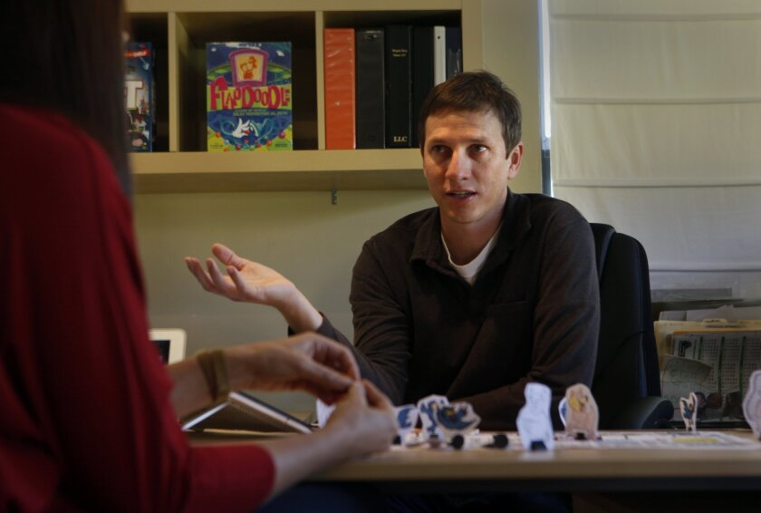 Matthew Rivaldi discusses the merits of a game he's testing out with his wife and co-creator, Jean, at their South Park home office last week.