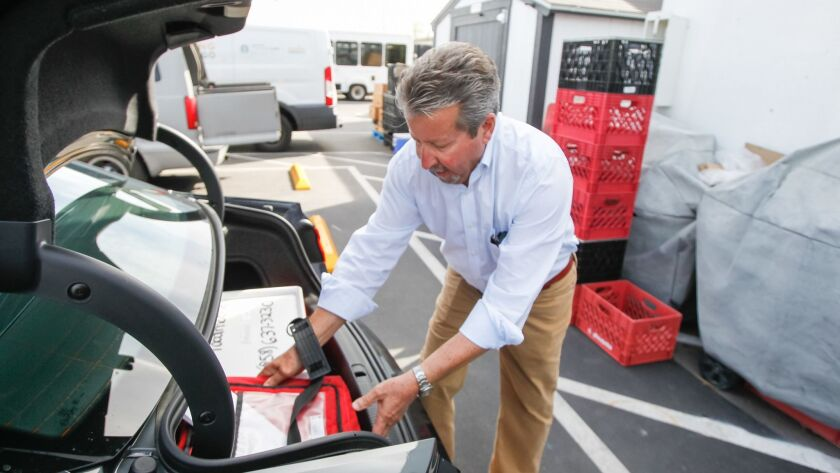 Longtime volunteer Louis Vener loads hot meals into his car at Jewish Family Service of San Diego for delivery to seniors and shut-ins on Wednesday in San Diego.