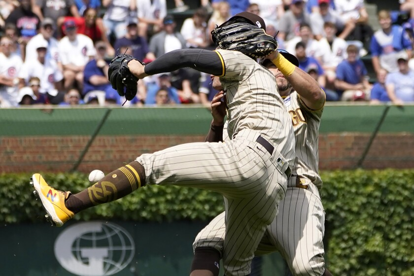 Padres shortstop Ha-seong Kim, foreground, and left fielder Tommy Pham collide going after a fly ball.