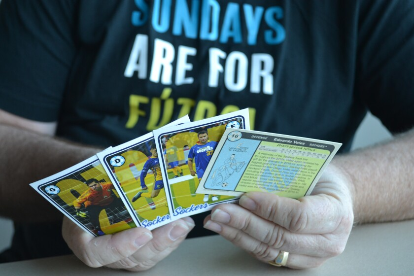 Travis Peterson holds the Sockers trading cards he designed.