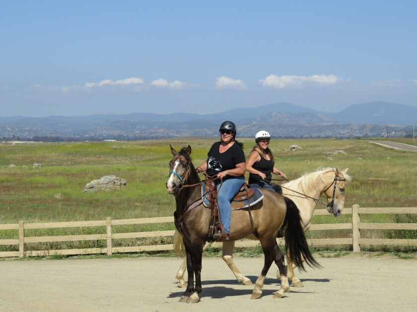 Lisa Crear (left) and Teresa Hiles, both of Ramona, get ready to ride through the Ramona Grasslands Preserve Thursday afternoon. The preserve will grow in size soon with the county's Board of Supervisors poised to purchase an additional 123-acre parcel to add to the county park's holding, making the preserve more than 3,600 acres large.