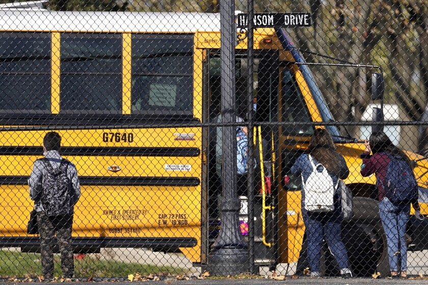 Students wait to board a school bus