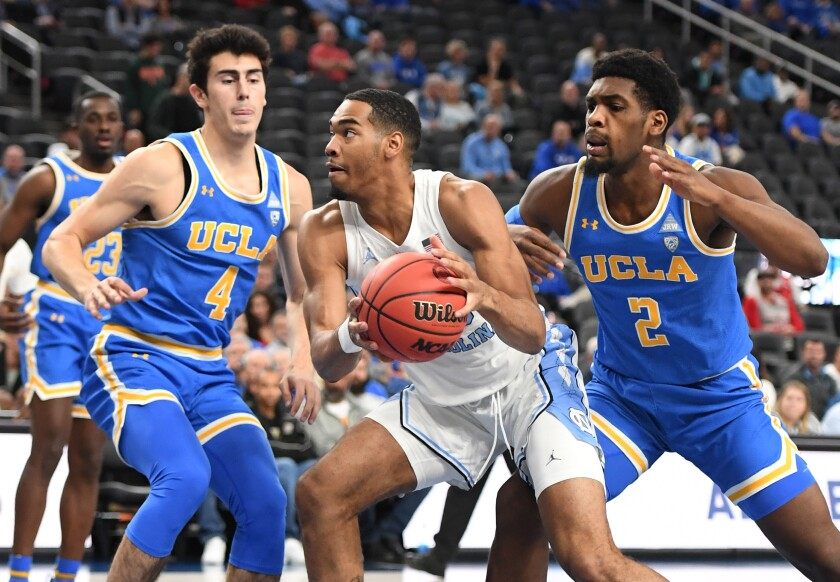 North Carolina's Garrison Brooks drives to the basket between UCLA's Jaime Jaquez Jr., left, and Cody Riley on Saturday in Las Vegas.