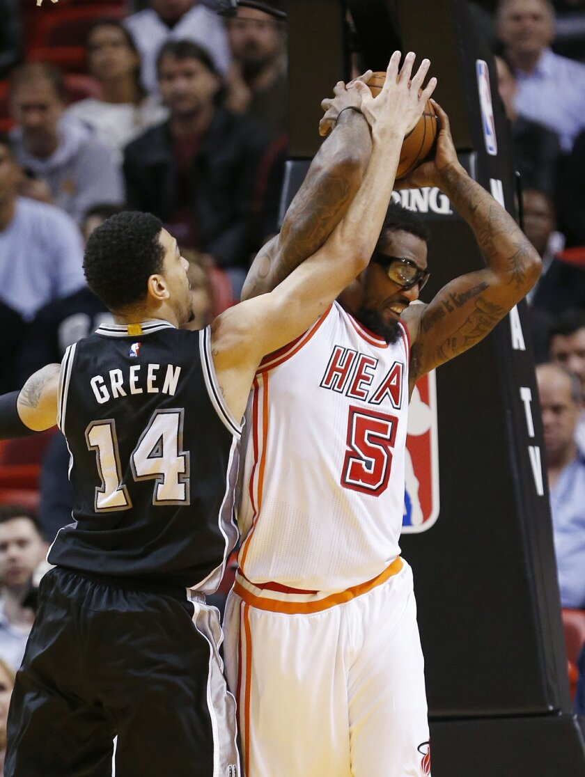 Miami Heat forward Amar'e Stoudemire (5) and San Antonio Spurs guard Danny Green (14) battle for a rebound during the first half of an NBA basketball game, Tuesday, Feb. 9, 2016, in Miami. (AP Photo/Wilfredo Lee)
