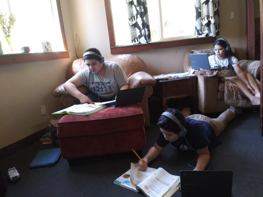 Vallecitos students Roman, Christian and Sophia Ortiz do their schoolwork with the help of headphones donated by JLab Audio.