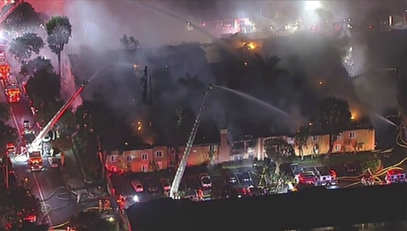 This image provided by KABC-TV shows firefighters battling a blaze at an apartment complex on Wednesday, Feb. 12, 2020 in Tustin, Calif. The blaze was reported in one two-story building in the Chatham Village apartment complex around 3 a.m. and the roof collapsed 25 minutes later. More than 100 firefighters battled the fire and none were injured. (KABC-TV via AP)
